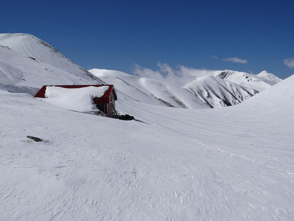 雪に埋もれた双六冬期小屋、笠ヶ岳を遠望